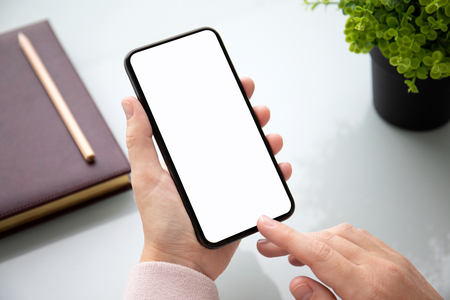 female hand holding touch phone with isolated screen above the table in the office Фото со стока