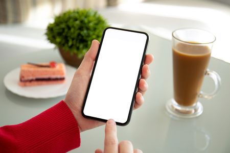 female hands holding phone with isolated screen above the table in a cafe Фото со стока
