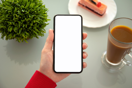female hand holding phone with isolated screen above the table in a cafe