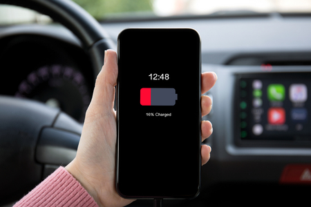 women hand holding phone with low charged battery on screen in the car Фото со стока