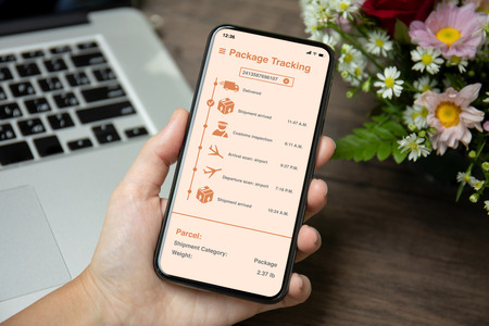 female hand holding phone with app tracking delivery package on the screen over desk with laptop and flowers Фото со стока