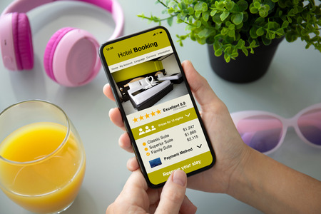 female hands holding phone with app hotel booking on the screen above the table with headphones
