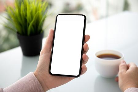 weibliche Hände, die Telefon mit isoliertem Bildschirm in einem Sommercafé halten holding Standard-Bild