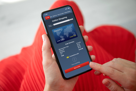 female hands in red dress holding phone with app online shopping on the screen