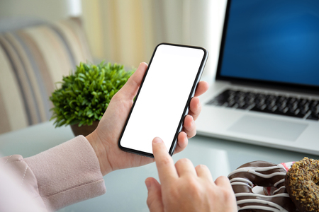 female hands holding phone with isolated screen above the table in the office Фото со стока