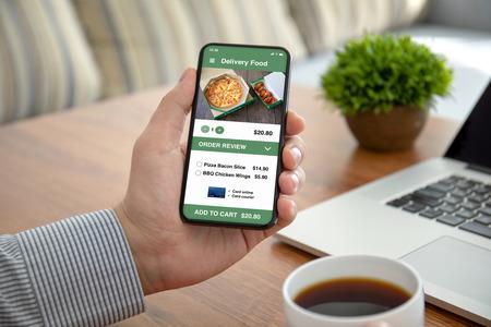 mannelijke handen met telefoon met app-bezorgvoedsel op het scherm boven de tafel op kantoor