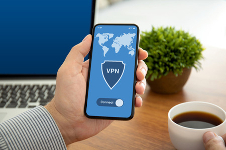 male hands holding phone with app vpn on the screen above the table in the office