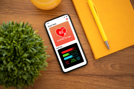 touch phone with app heart and activity on the screen on yellow office table
