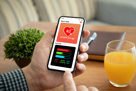 male hands holding phone with app heart and activity on the screen above table in office Фото со стока