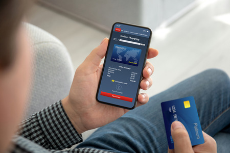 male hands holding phone with app online shopping on the screen and a credit card