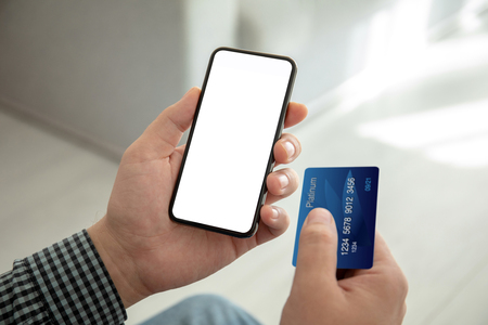 male hands holding phone with isolated screen and a credit card