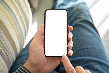 male hands holding phone with isolated screen in the room on the sofa Фото со стока