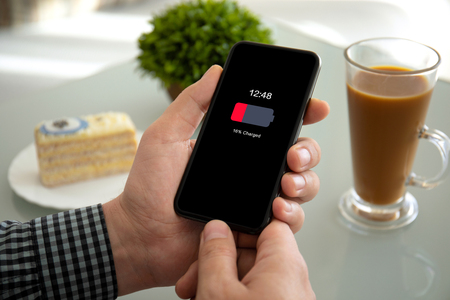 male hands holding phone with low charged battery on screen above the table in a cafe Фото со стока