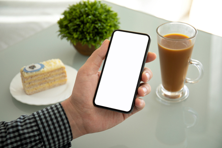 male hands holding phone with isolated screen above the table in a cafe