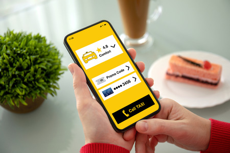female hand holding phone with app call taxi on the screen above the table in a cafe