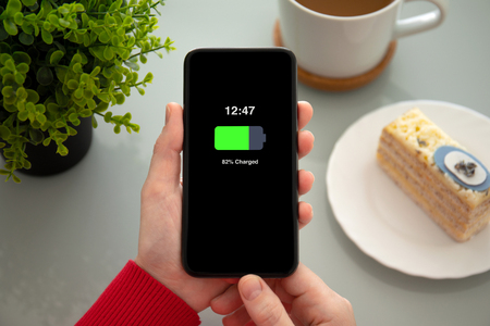 female hands holding phone with charged battery on the screen above the table in a cafe