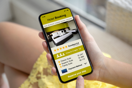 female hands in yellow dress holding phone with app hotel booking on the screen