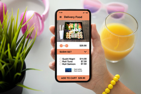 female hand holding phone with app delivery food on the screen with headphones glasses and juice