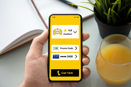 male hand holding phone with app call taxi on the screen above table in office