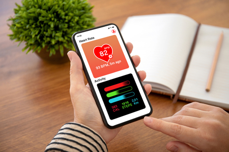 female hands holding phone with app heart and activity on the screen above table in office