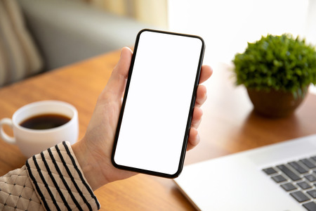female hands holding phone with isolated screen above the table in the room Stock Photo