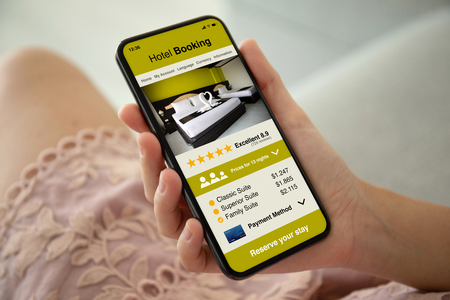 female hands in pink dress holding phone with app hotel booking on the screen Фото со стока