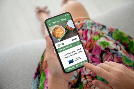 women hands in colored dress holding phone with app delivery food on the screen