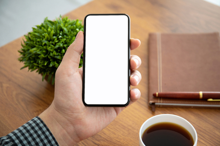 male hands holding phone with isolated screen above the table in office Фото со стока