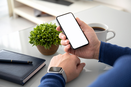 man hands with watch holding phone with isolated screen above the table in the office