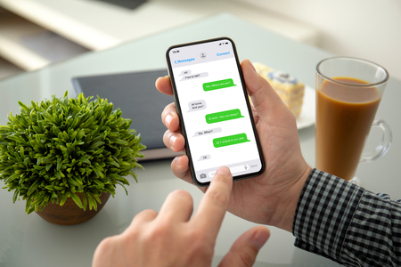 male hands holding phone with app messenger on the screen above the table in office
