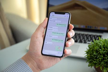 Alushta, Russia - 9 ottobre 2018: Uomo che tiene iPhone X con servizio di social network WhatsApp sullo schermo. iPhone 10 è stato creato e sviluppato da Apple inc.