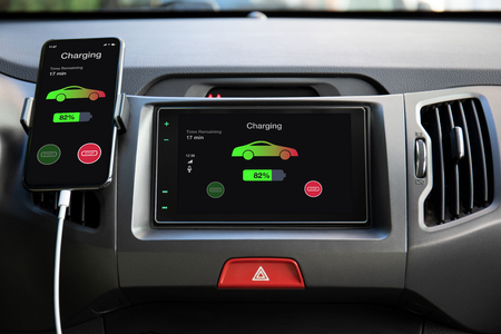 phone in eco electric car touch multimedia system with charging battery on the screen Stock Photo