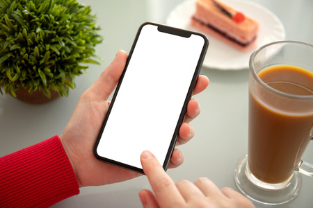 female hands holding phone with isolated screen above the table in a cafe Stock Photo