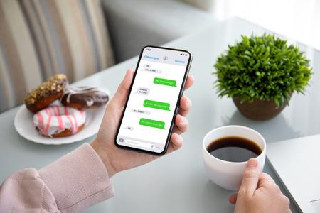 manos femeninas sosteniendo el teléfono con la aplicación messenger en la pantalla sobre la mesa en un café Foto de archivo