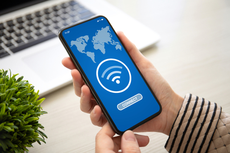 vrouwelijke handen met telefoon met app wifi verbinden op het scherm boven de tafel op kantoor