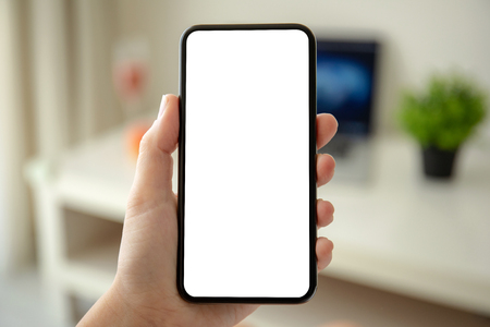 female hands holding phone with isolated screen in the house in room