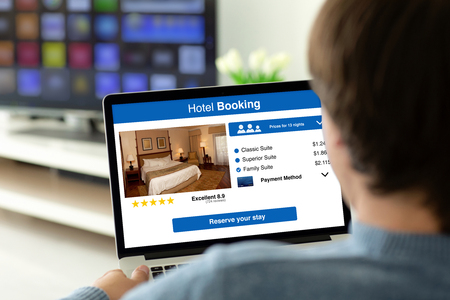 man holding laptop with app hotel booking on the screen in the house in the room