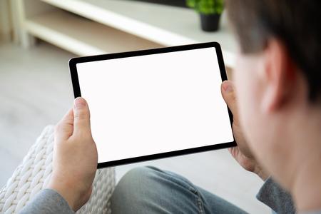Manos de hombre sosteniendo tableta de computadora con pantalla aislada en la sala de inicio