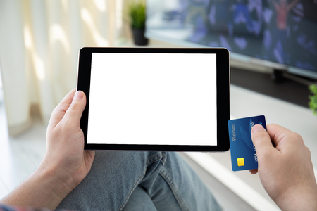 male hands holding bank card and computer tablet with isolated screen in the house in the room Imagens