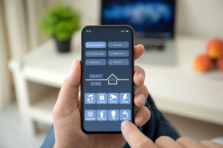 man hands holding phone with app smart home on the screen in the house in room Stockfoto