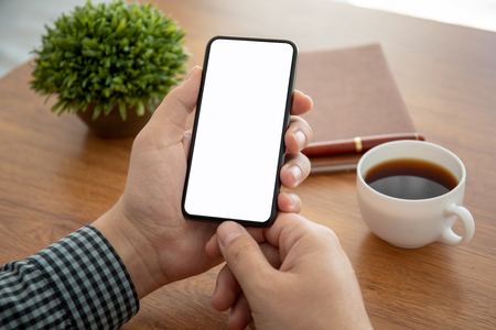 male hand holding phone with isolated screen above the table in office