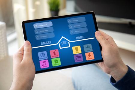 Manos de hombre sosteniendo la tableta de la computadora con la aplicación de inicio inteligente en la pantalla de la sala de inicio Foto de archivo
