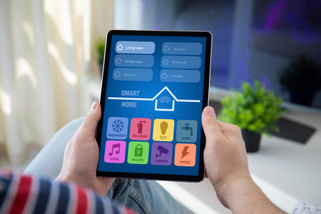 man hands holding computer tablet with app smart home on screen in the home room Stockfoto