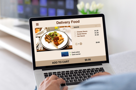 male hands on keyboard laptop with app delivery food on the screen in the house in room