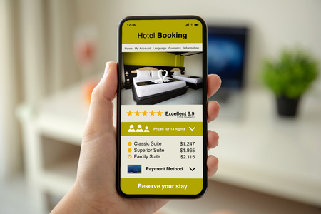 female hands holding phone with app hotel booking on the screen in the house in room Stockfoto