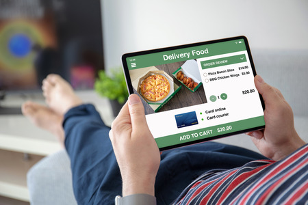 man hands holding computer tablet with app delivery food on screen in the home room