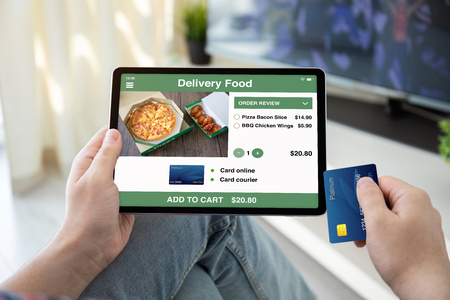 male hands holding bank card and computer tablet with app delivery food on screen in house in the room