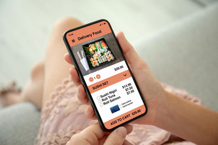 female hands in pink dress holding phone with app delivery food on the screen Stockfoto