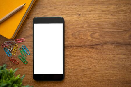 touch phone with isolated screen on a wooden table in the office