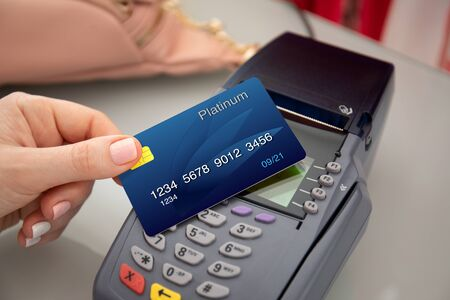 Woman hand holding plastic card and pay pass online terminal shopping at a store Imagens